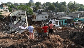 Sri Lankan residents survey damaged homes at the site of a collapsed garbage dump in Colombo