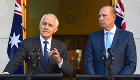 Australia's Prime Minister Malcolm Turnbull speaks as Immigration Minister Peter Dutton listens
