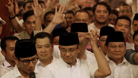 Former Indonesian education minister Anies Baswedan (C) holds the hand of Gerindra party chief Prabo