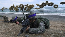 South Korean Marines take position on a beach as amphibious assault vehicles fire smoke shells