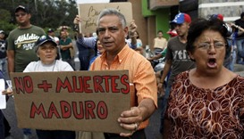 """People holding a placard that reads """"No more deaths, Maduro"""" gather outside the wake of Paola Ramire"""