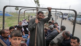 Displaced Iraqi men wait in a truck to be transported to a camp as the battle between the Iraqi Coun