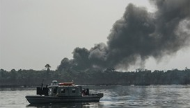 A cloud of smoke rises from an illegal oil refinery  in the Niger Delta region