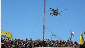 Kurds wave flags as a medical helicopter, from the US-led coalition, flies over the site of Turkish