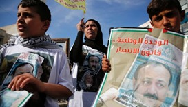Palestinians hold portraits of Palestinian leader and prominent prisoner Marwan Barghouti