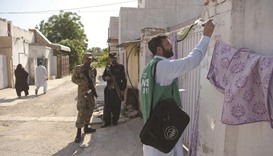 An official from the Pakistan Bureau of Statistics  marks a house after collecting information from