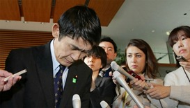 Surrouded by reporters, Japan's Disaster Reconstruction Minister Masahiro Imamura bows after submitt