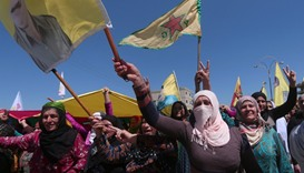 Kurdish women carry flags as they protest, in the northeastern city of Qamishli