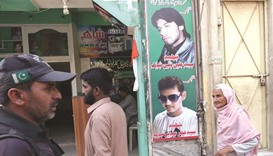 A policeman (left) and residents walk past a shop displaying the pictures of men, who were killed in