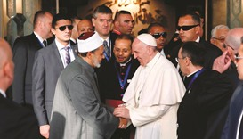 A handout picture released by Egypt's Al-Azhar Media Centre shows Pope Francis shaking hands with Sh