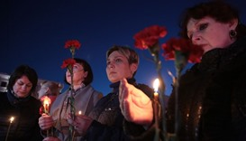 Women hold flowers and lit candles as they take part in a gathering in memory of victims of the blas