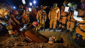 Colombian civil defense workers bury the coffin of Jesus Diago, 33, who died rescuing his family dur