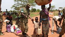 A Uganda People's Defence Forces soldier receives South Sudanese refugees crossing into Uganda at th