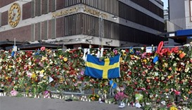 Swedish police conduct raids after truck attack kills four