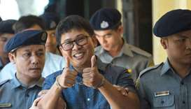 Detained  journalist Wa Lone (C) gives a thumbs up to reporters as he is escorted by police to a cou