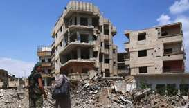 A Syrian government forces soldier talks with a woman in a destroyed street in the former rebel-held