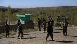 Afghan security personnel keep watch at the site of an attack by Taliban militants on a government c