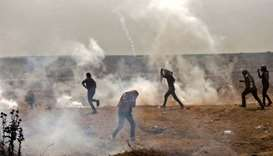 Palestinians take cover from tear gas smoke during clashes with Israeli security forces near border