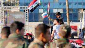 A Syrian soldier waves Russian and Syrian flags during a protest against air strikes in Damascus