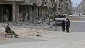 Civilians walk in the former Syrian town of Douma on the outskirts of Damascus