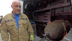Demolition expert Roger Flakowski poses next to another defused World War II bomb