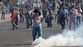A demonstrator reacts to a tear gas canister during a protest over a controversial reform to the pen