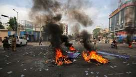 Police officers patrol a street after people belonging to the Dalit community burned tyres and hoard