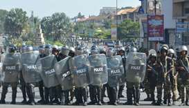 Riot police walk in formation as they prepare to disperse opposition demonstrators protesting agains