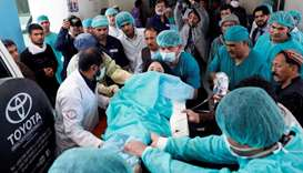 Medics carry an injured woman to the ambulance at a hospital after a suicide attack in Kabul, Afghan