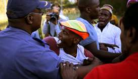 A police officer restrains a protester during protests in Mahikeng, in the North West province, Sout