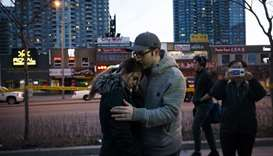 People embrace at the scene of a memorial for victims of a crash at Yonge St. at Finch Ave., after a