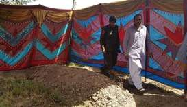 Pakistani policemen walk beside the grave of Italian national of Pakistani origin Sana Cheema