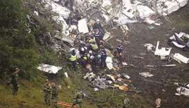 Rescue crew work in the wreckage from a plane that crashed into Colombian jungle with Brazilian foot