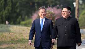 North Korea's leader Kim Jong Un (R) and South Korea's President Moon Jae-in (L) walk together