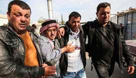 The father (C-R) of Palestinian teenager Azzam Oueida is consoled by others as he walks outside the