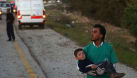 An injured Syrian boy is carried by a medical volunteer following the arrival of buses carrying Jais