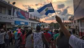 A migrant flutters a Guatemalan national flag during a march