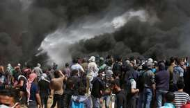 Palestinian demonstrators gather at the Israel-Gaza border during clashes with Israeli troops