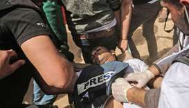 Demonstrators assist an injured Palestinian journalist Yasser Murtaja during clashes with Israeli se