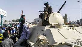 Sudanese protesters salute a military armoured vehicle