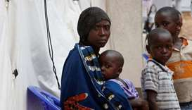 A Congolese woman and her children who are suspected Ebola patients sit at the Ebola treatment centr