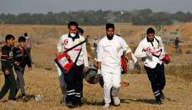 Palestinian paramedics carry an injured protester during a demonstration near the border between Isr