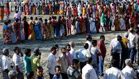 Voters line up to cast their votes outside a polling station during the first phase of general elect