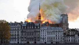 Seen from across the Seine River, smoke and flames rise during a fire at the landmark Notre-Dame Cat