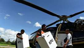 Officials carry election materials to be distributed by helicopter at Wamena airport in Jayawijaya,
