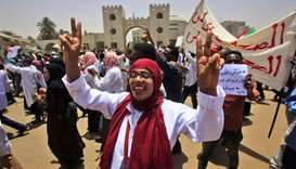 Sudanese demonstrators wave signs as they continue to protest outside the army complex in the capita