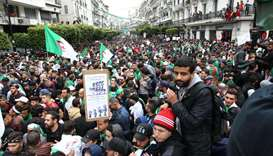 Algerians, waving national flags, march during an anti government demonstration in the capital Algie