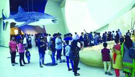 A whale shark overlooking throngs of visitors at the museum