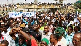 Sudanese protesters flash victory signs during a rally outside the army headquarters in the capital