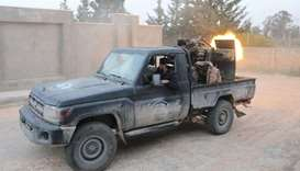 Members of the Libyan internationally recognised government forces fire during fighting with Eastern